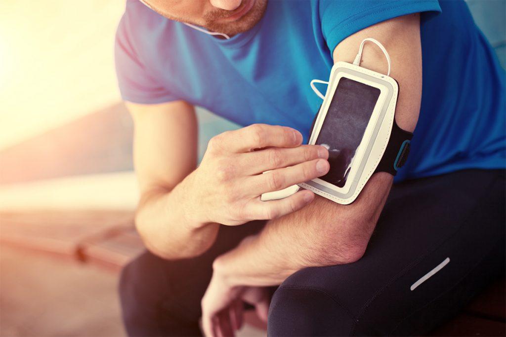 A runner prepares by choosing his playlist