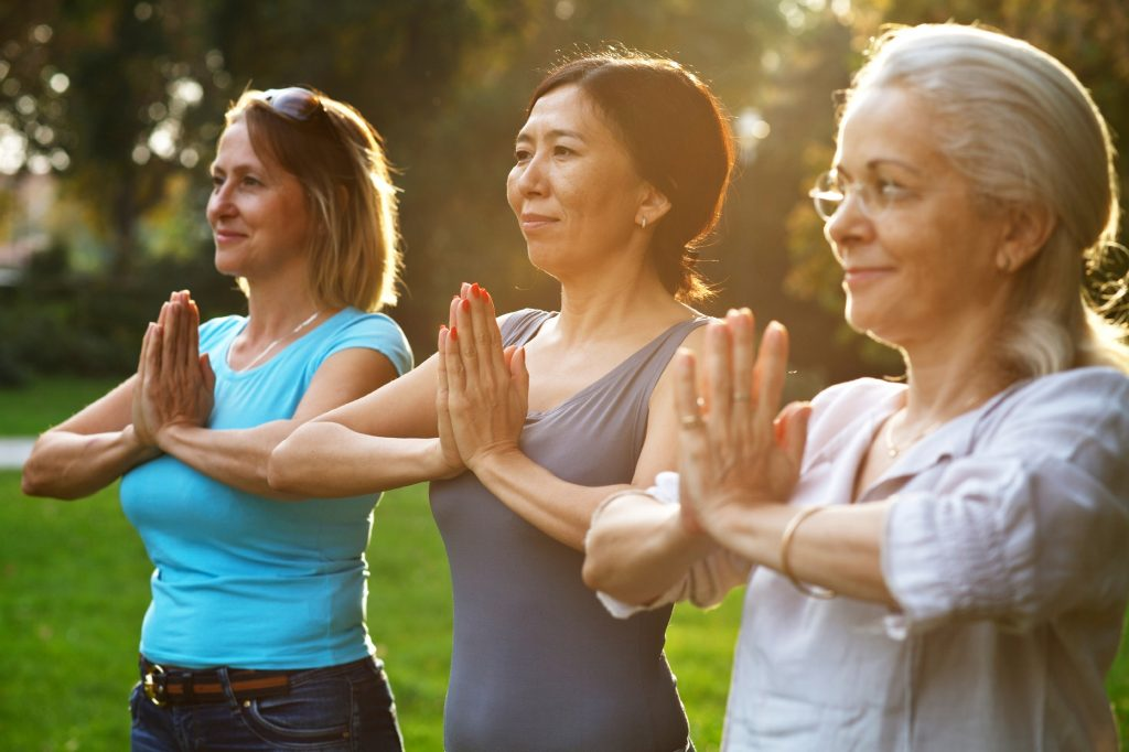 A group of mature women perform yoga outdoors