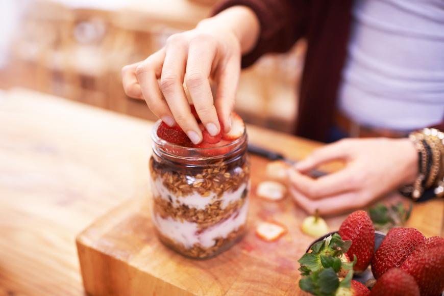 A person preparing a jar of overnight oats