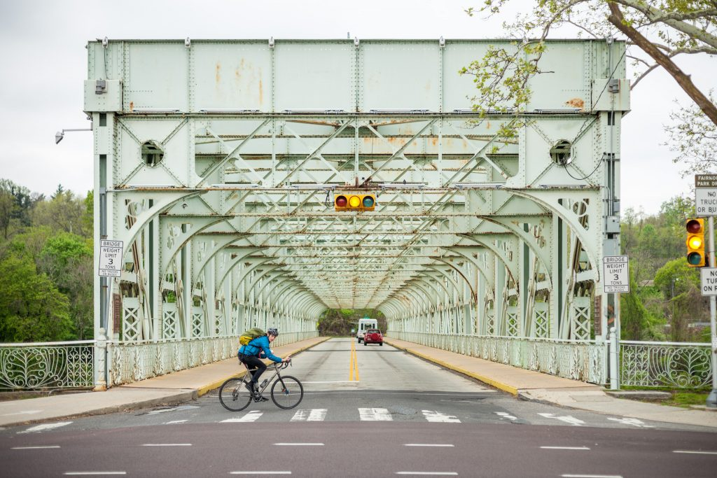 A cyclist biking past a bridge