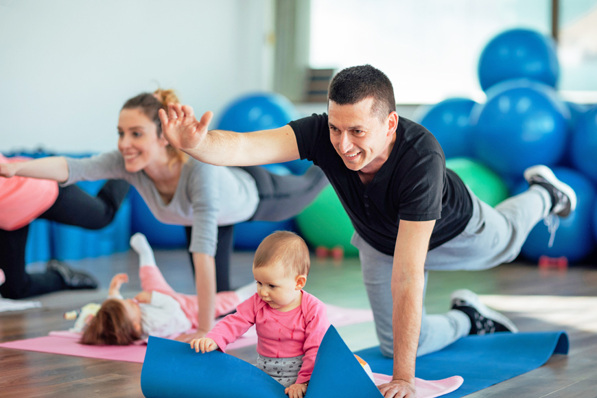 Parents taking an exercise class with their young children
