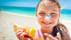 A little girl on the beach smiles with lots of sunscreen on her nose.