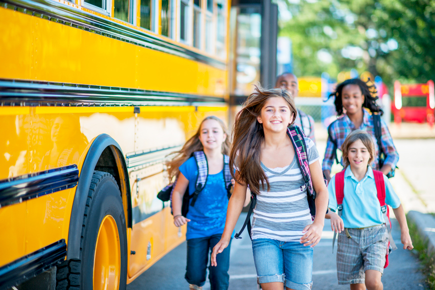 A group of smiling kids get off of the school bus