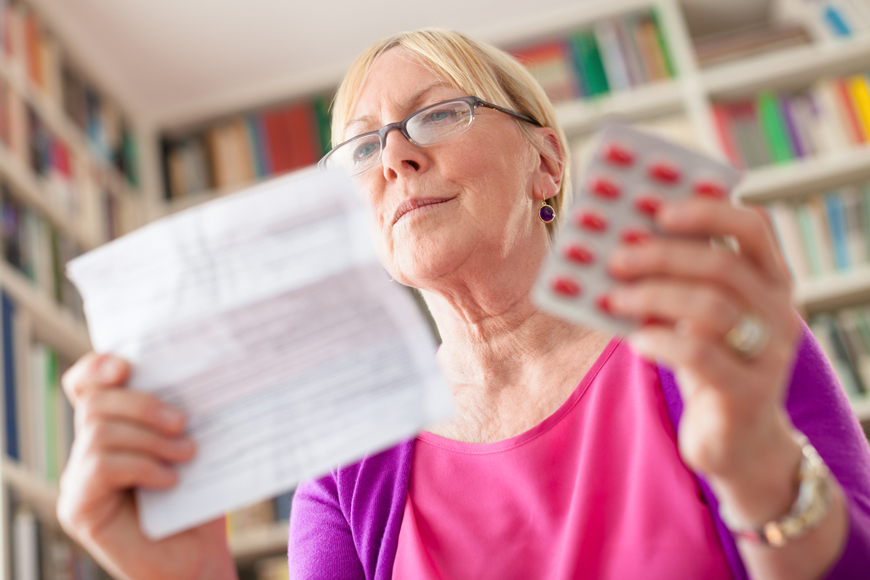 A woman reads the instructions for her prescription