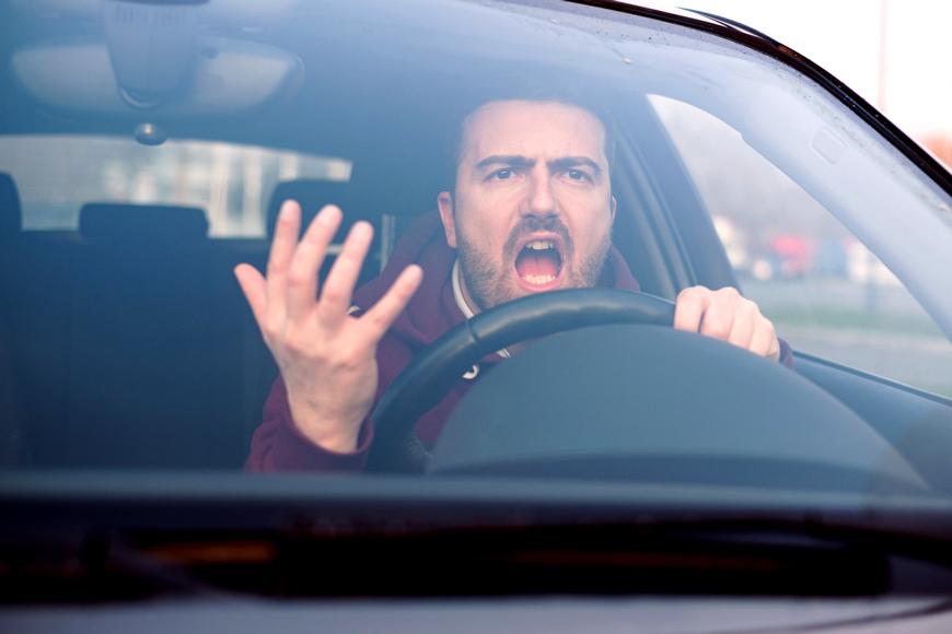 A man yells angrily while driving his car