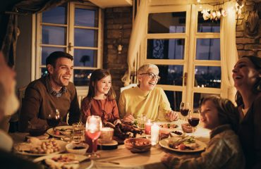 Cheerful multi-generation family talking during dinner at home.