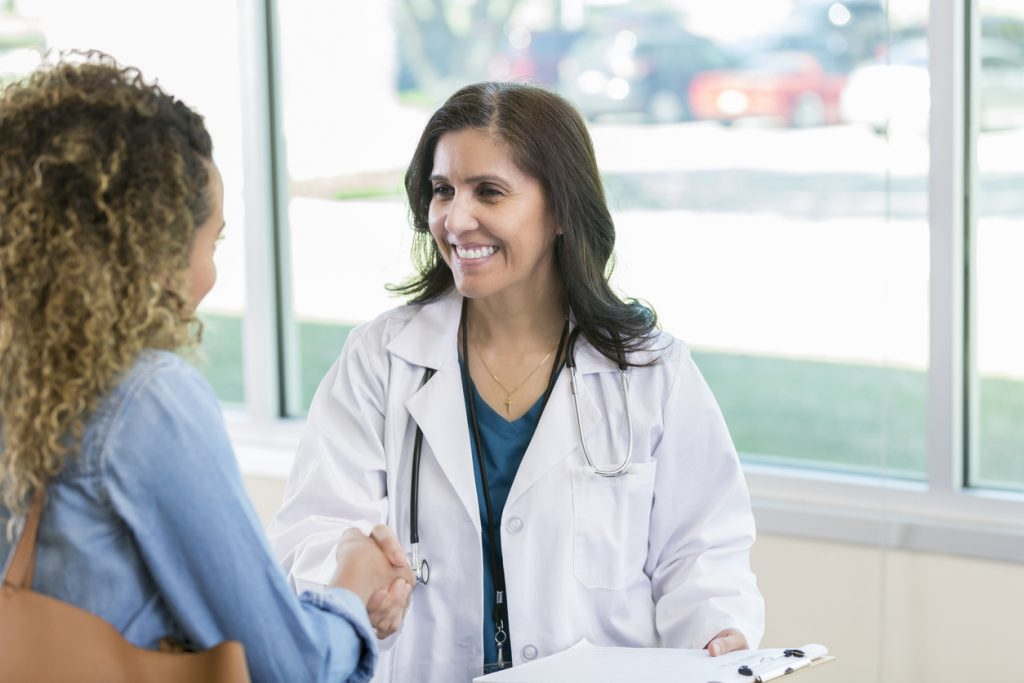 Confident mature Hispanic female doctor warmly greets a new female patient. They are shaking hands and are smiling at one another.