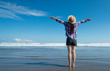 A woman stands before the ocean, with her arms outstretched