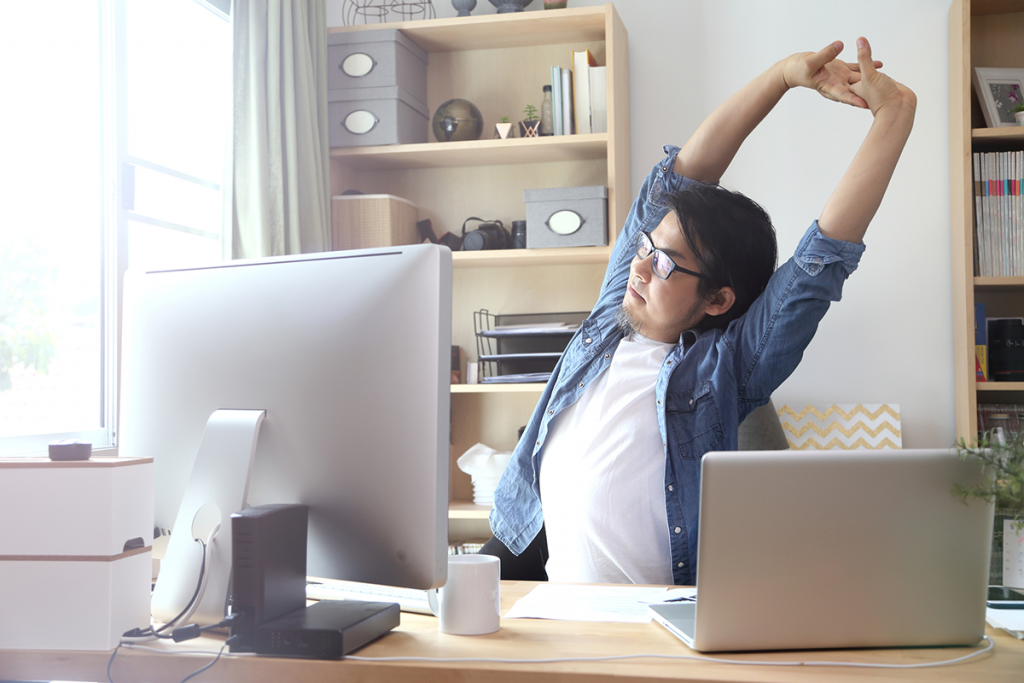 A young man stretches at the desk in his home office