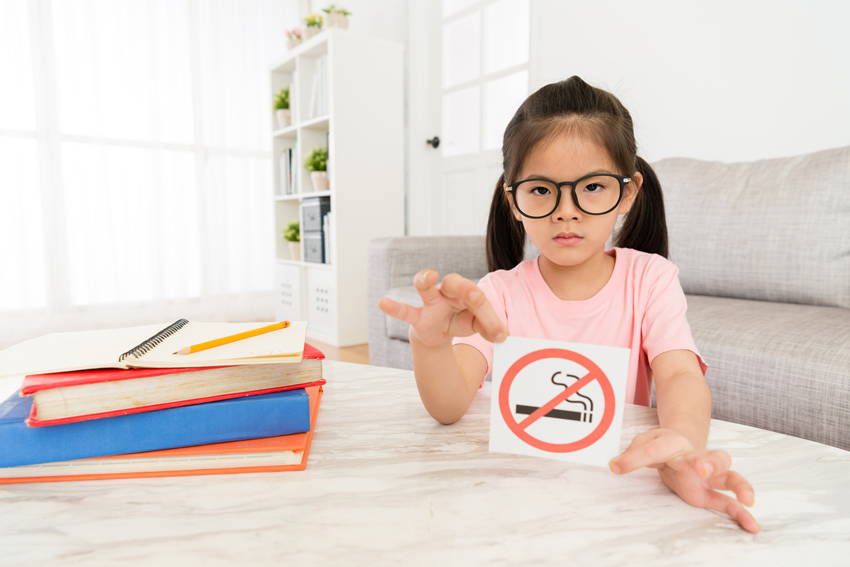 A young girl holds a No Smoking sign