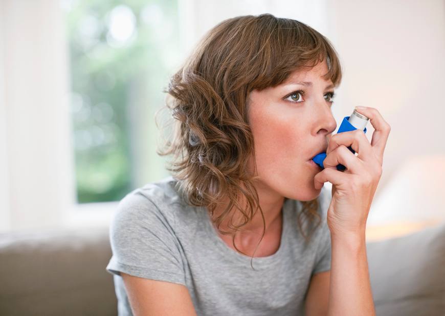 Woman taking her inhaler medication.