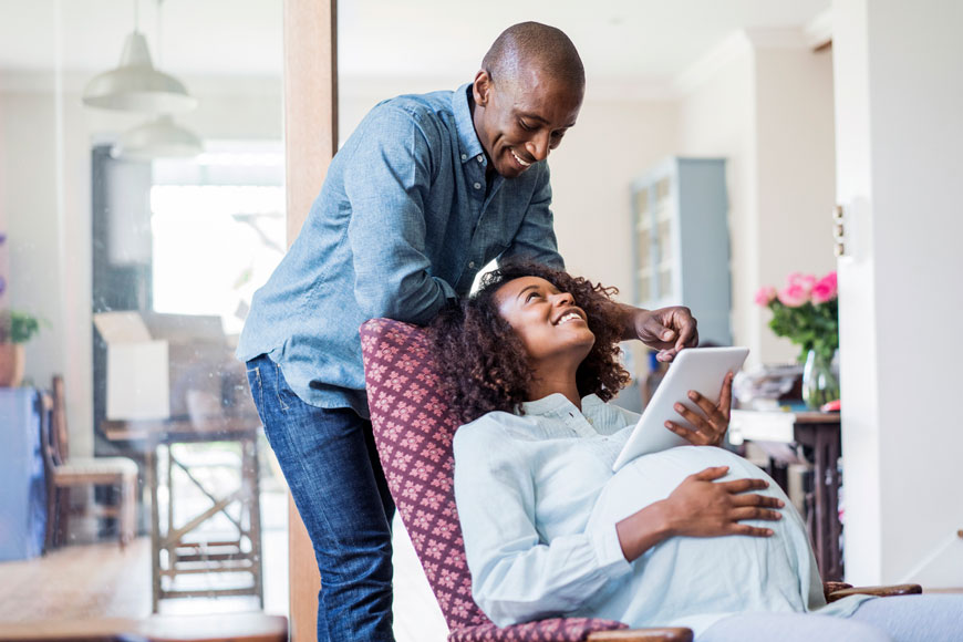 An expectant mother and father smile as they look at a tablet