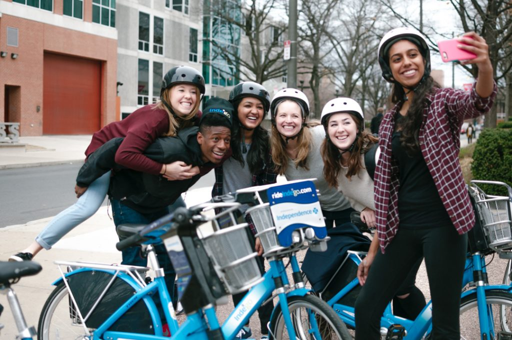 A group of young people takes a selfie with an Indego bike