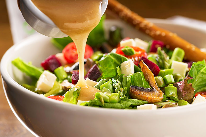 Dressing, being poured onto a salad