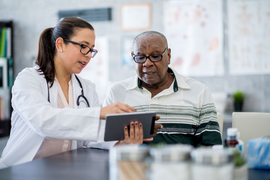A physician explains something on a tablet to her older patient