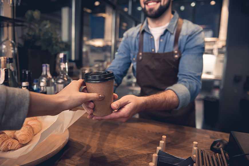 Barista hands customer coffee in a recycled paper cup with plastic lid.