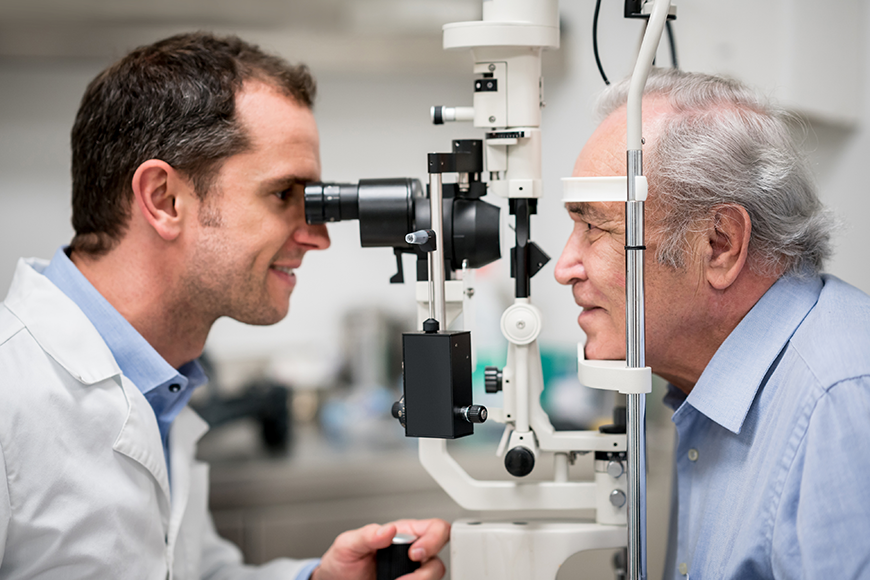 Optometrist giving an eye exam to a senior