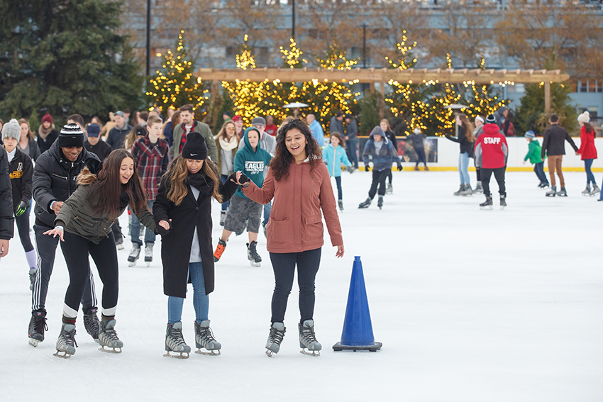 A group of skaters smiling on the ice rink