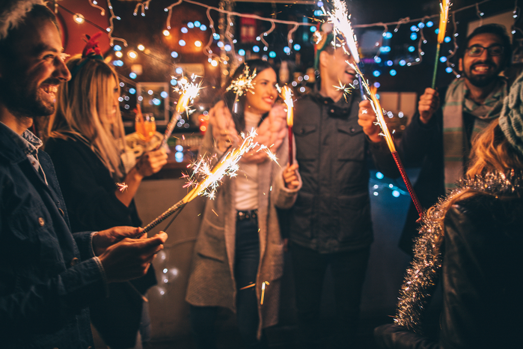 People celebrating New Year's Eve with sparklers outdoors