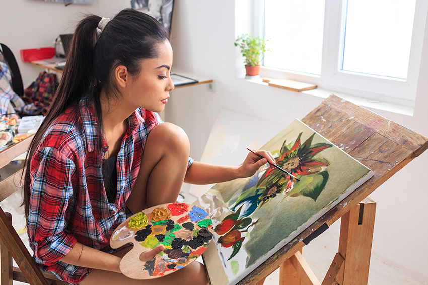 A young woman paints a picture of some flowers