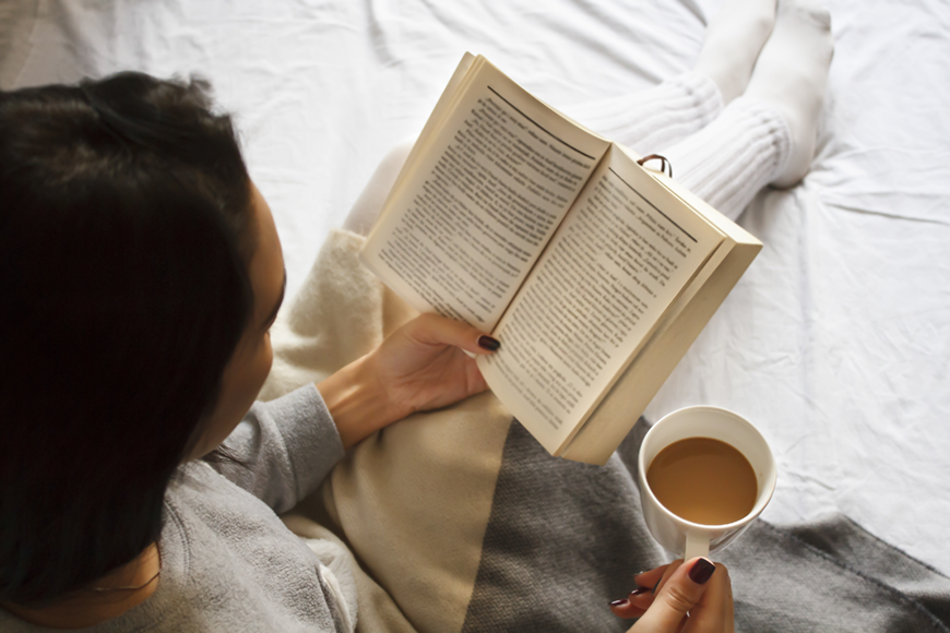 Overhead photo of a woman practicing self-care by drinking coffee and reading in bed.