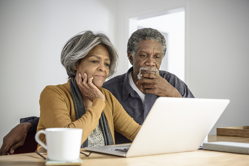 An older couple considers something carefully on their laptop computer.