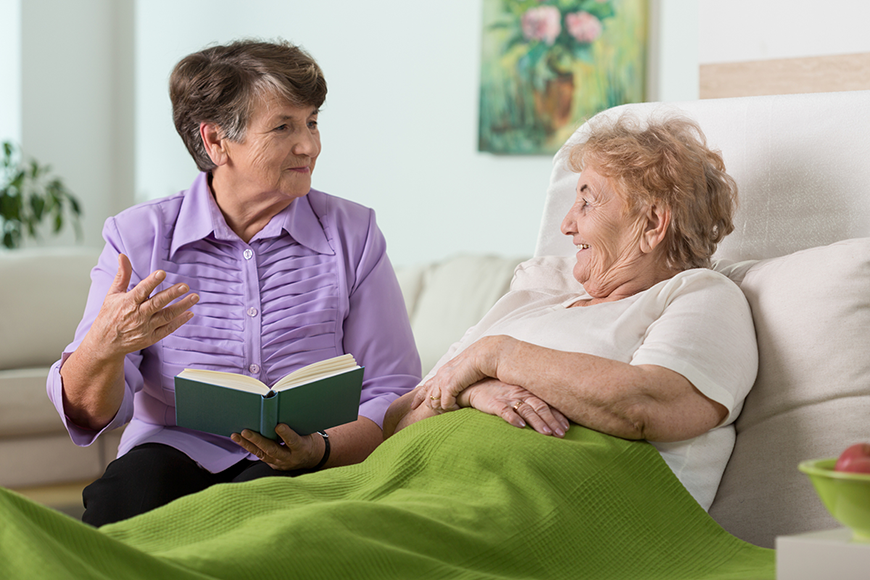 An older woman reads to her friend, who's in a hospital bed