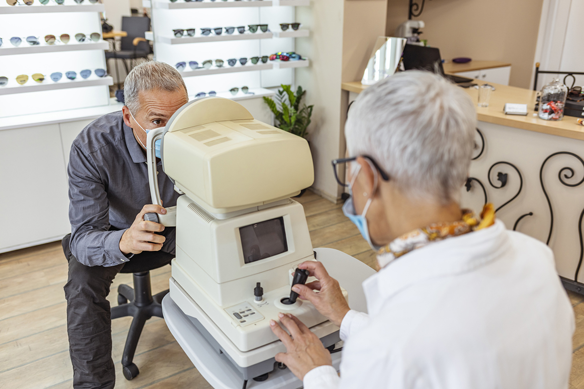 Senior optometrist looking through the special medical equipment and examining her mature patient's eyesight