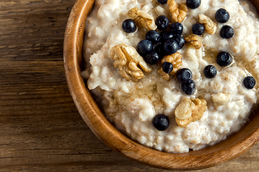 Oatmeal in a wooden bowl, topped with walnuts and blueberries.