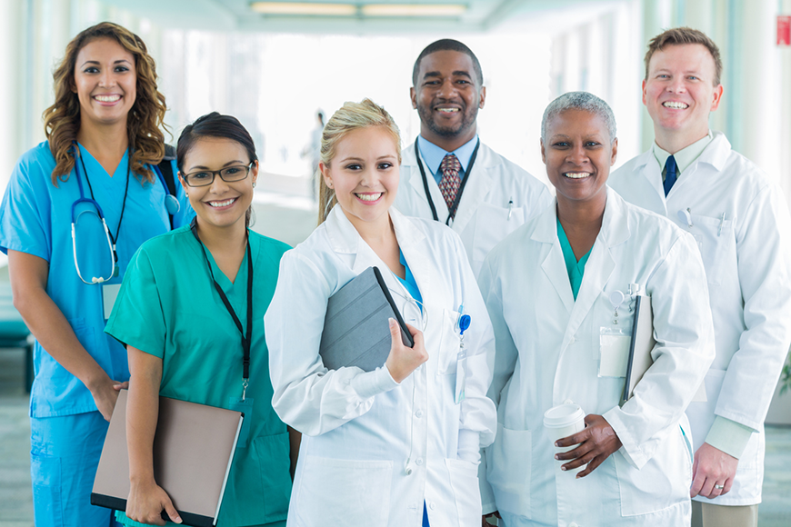 A diverse team of medical professionals smiles at the camera