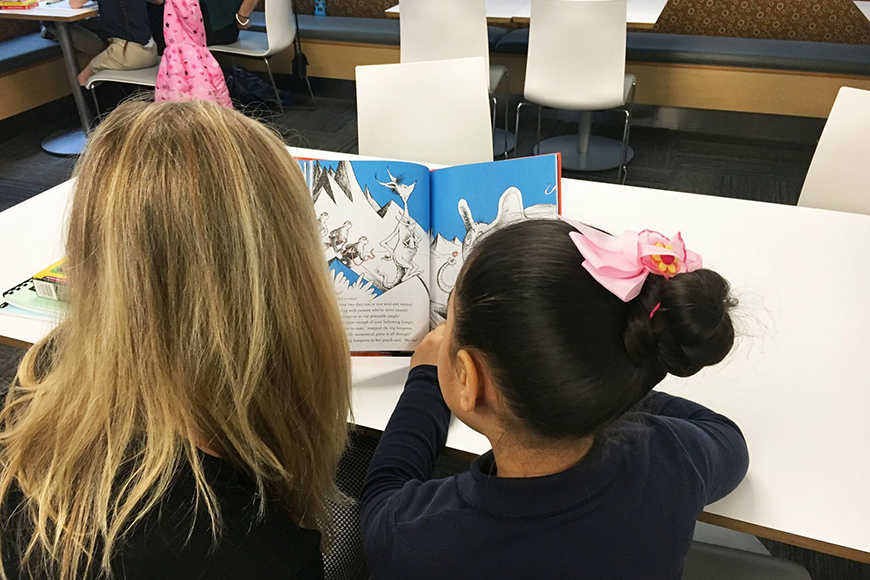 A woman from the Blue Crew reads to a young girl.