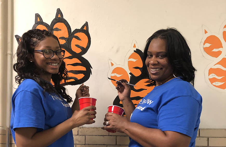 Deanne Riley-Giddins and her daughter, painting at a volunteer event
