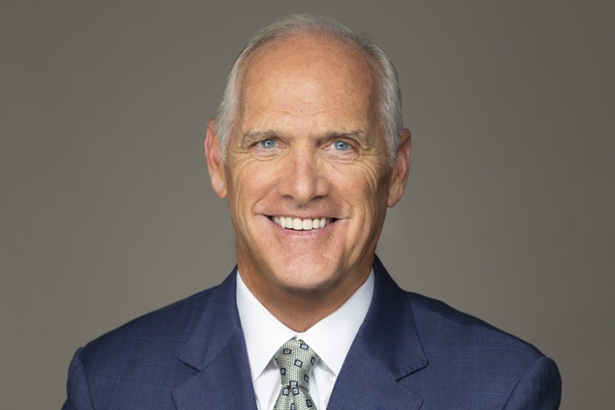 Headshot of Dan Hilferty smiling directly into the camera. He is a white man with blue eyes and white hair, wearing a blue suit jacket, white dress shirt, and grey patterned tie.