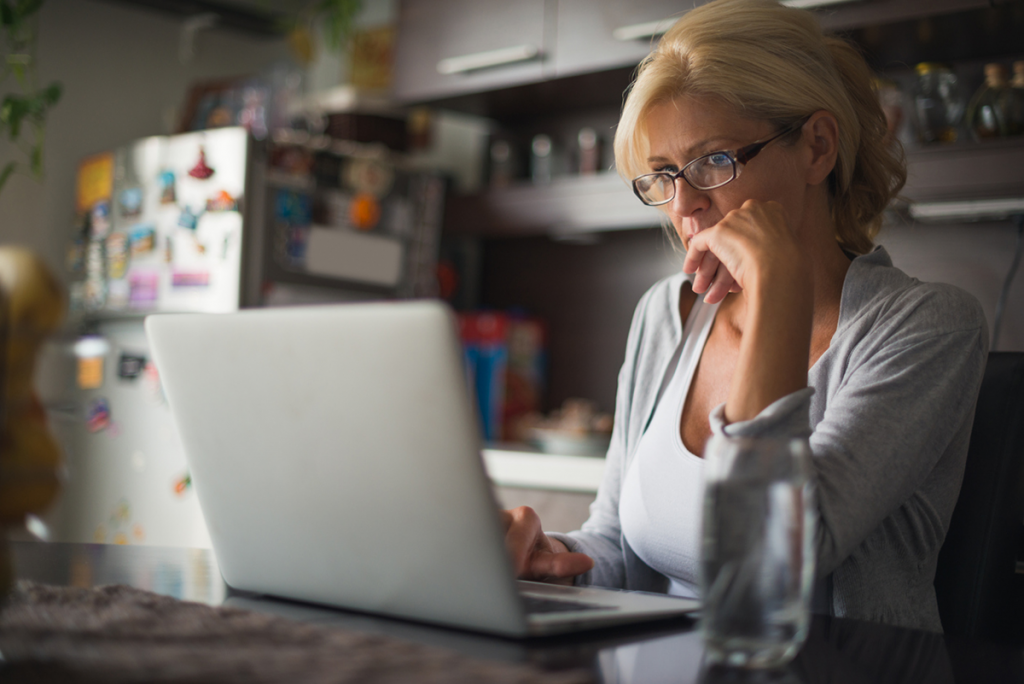Photo of a woman looking at a laptop computer in her kitchen