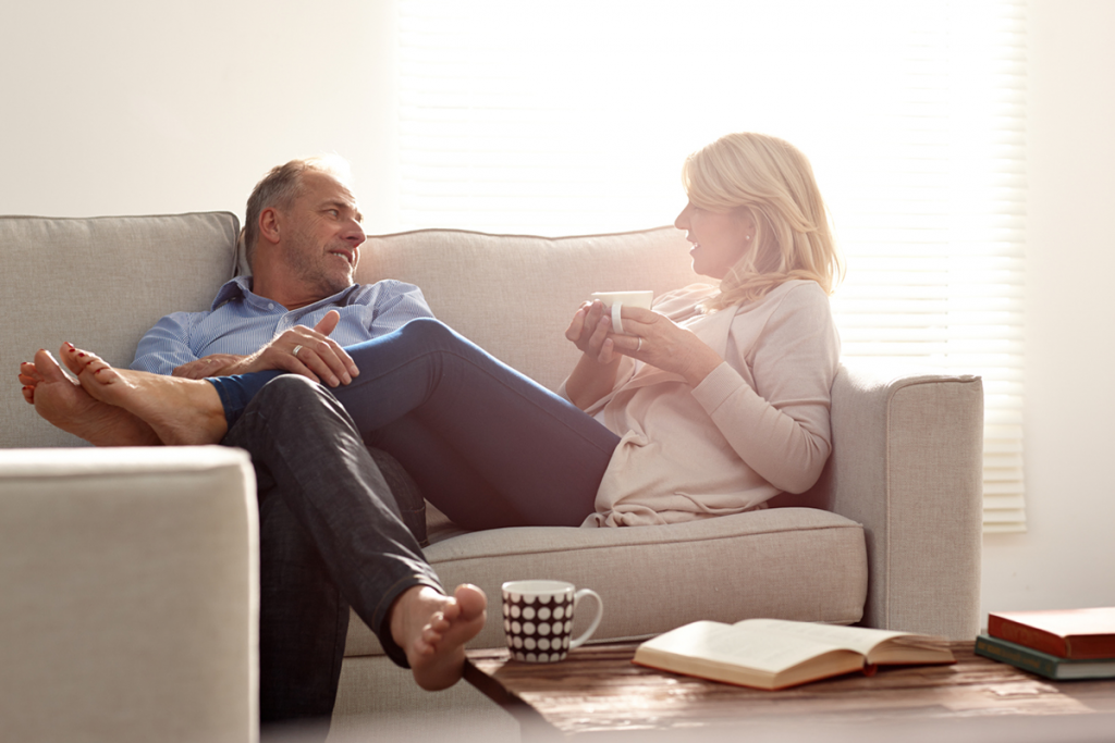 A mature couple sits on the couch, enjoying coffee and each other's company.