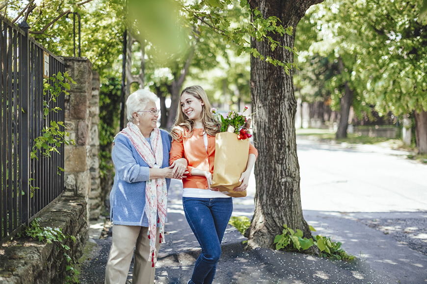 A young woman is helping an older woman with her groceries, walking down a tree-lined street.