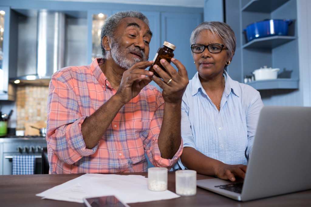 An older man examines a medication bottle, as woman uses a laptop