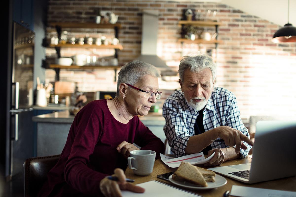 An older couple examines a bill and their laptop while seated at the kitchen table