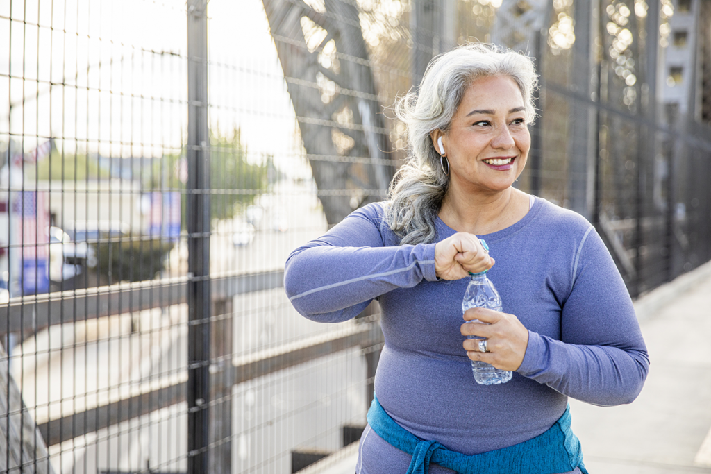 A woman smiles while opening a bottle of water on a bridge during her workout.