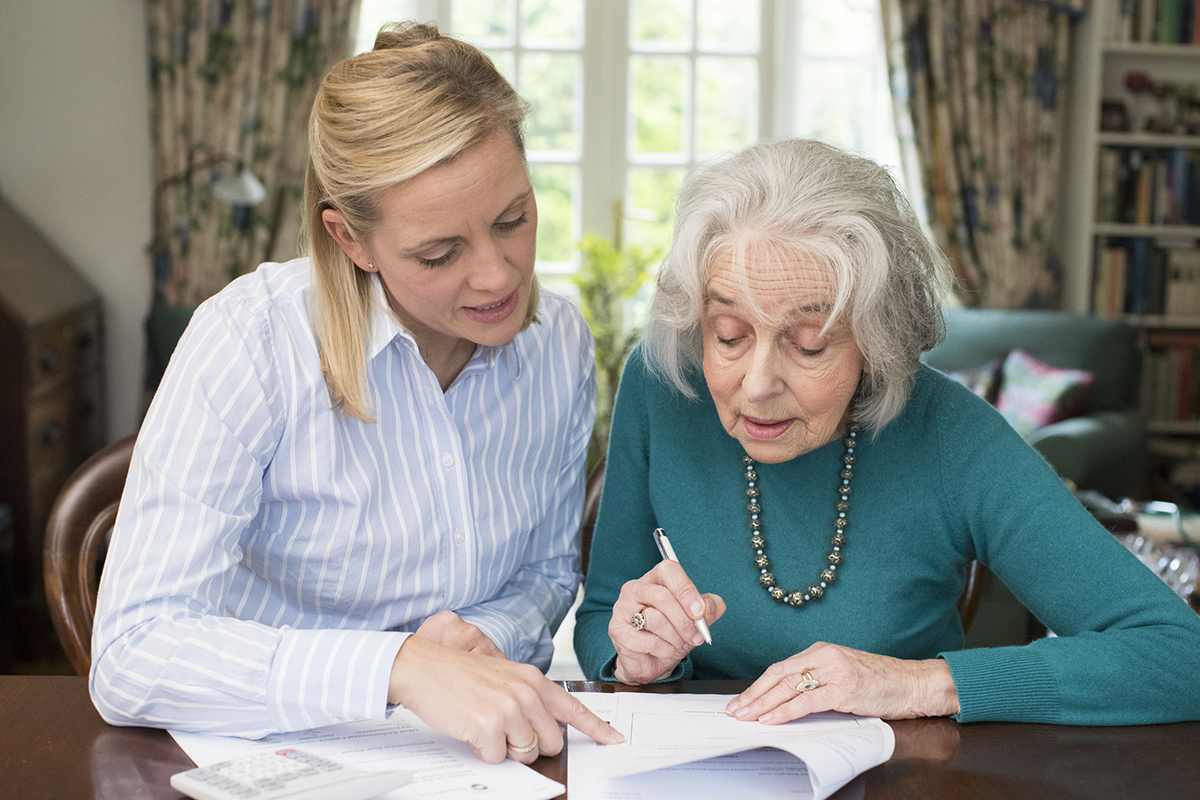 A woman helps an elderly woman go over some documents.