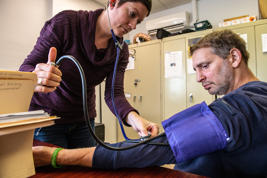 Kate Gleason-Bachman, taking a patient's blood pressure.