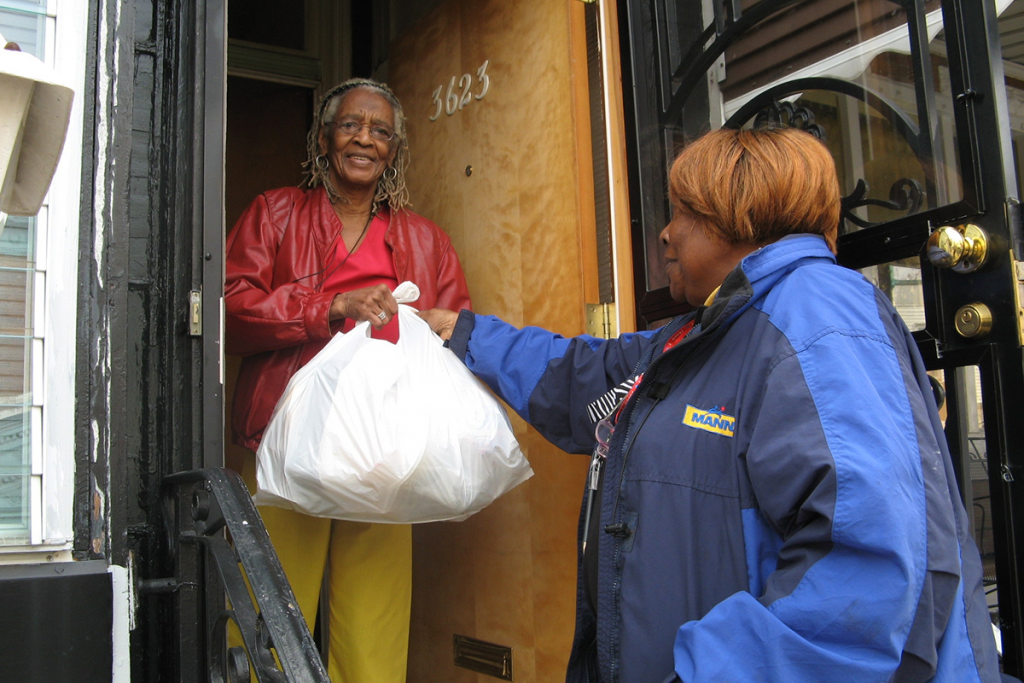 A senior woman receives a delivery of food from MANNA