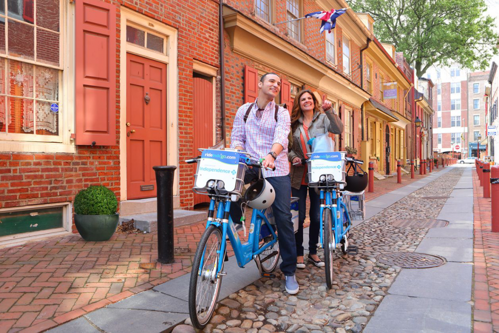 A couple enjoys historic buildings from atop bicycles.