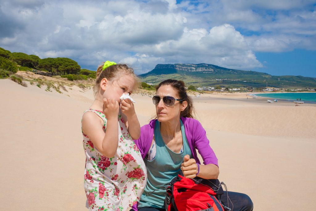 A little girl blows her nose on the beach, as her mother comforts her.