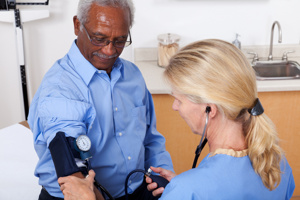 An older man having his blood pressure checked at the doctor's office.