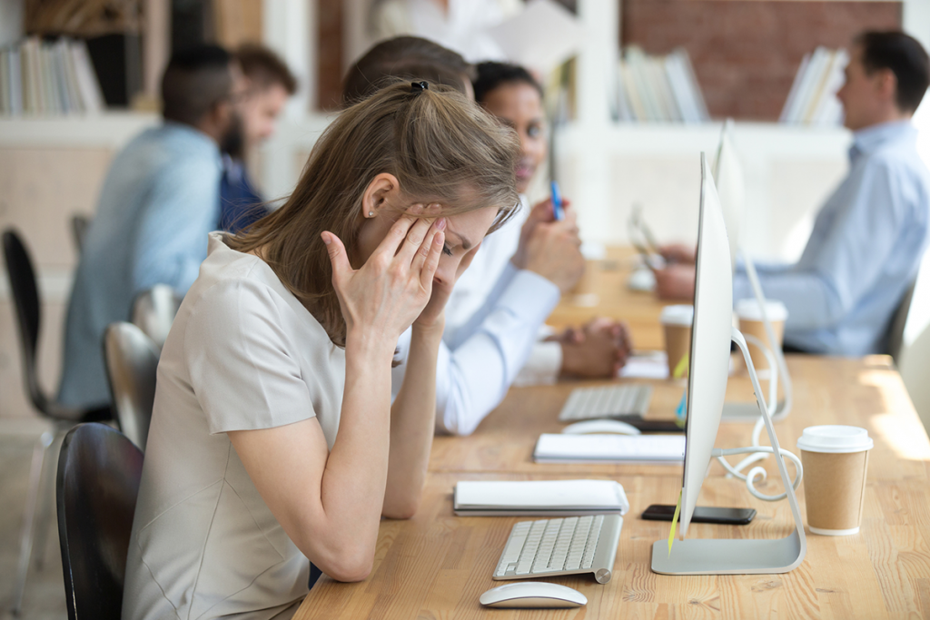 A young woman looking very stressed in an office