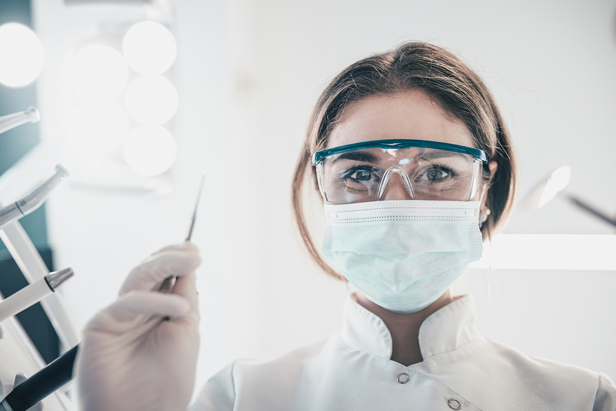 A close up of a masked dentist holding her tool