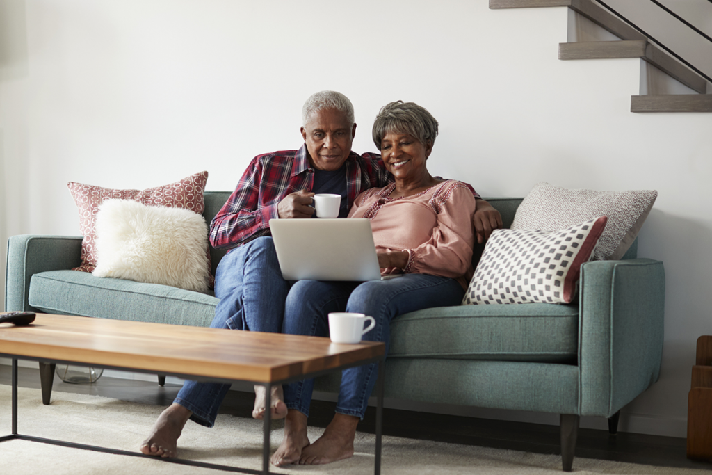 An older couple sits on the couch, looking at a laptop computer together