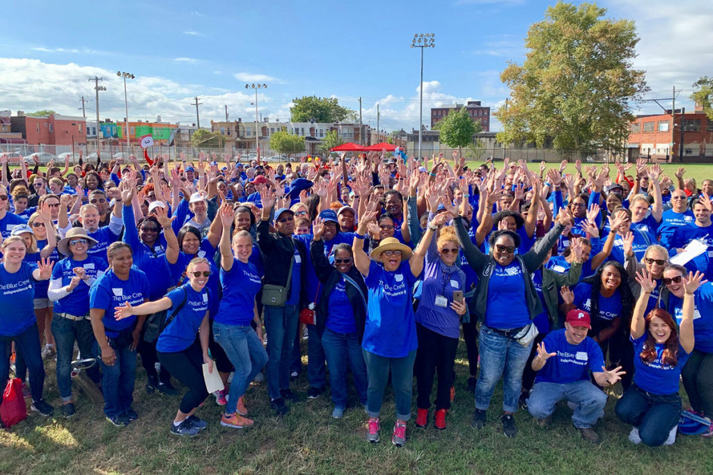 A large group of Blue Crew volunteers waving at the camera.
