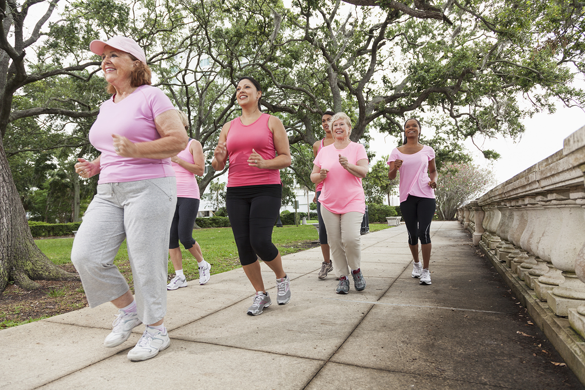 A group of women wearing pink and walking for breast cancer awareness.